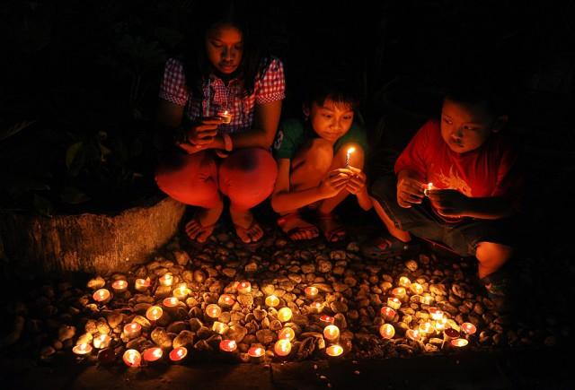 Unos niños colocan velas para celebrar el nuevo año en Surabaya, Indonesia. By ROBERTUS PUDYANTO (GETTY)